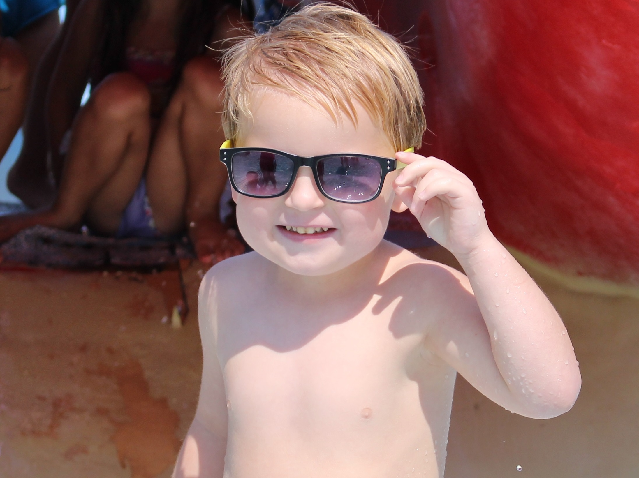 Little boy wearing sunglasses smiling in a happy harbor pool.