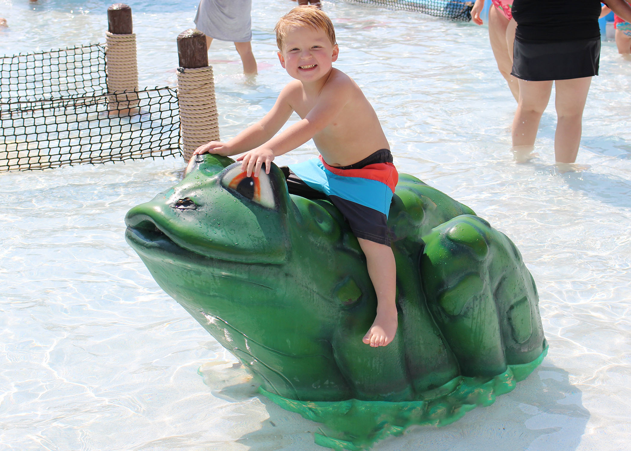 Little boy sitting and smiling on large green frog in our Happy Harbor.