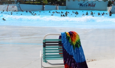 Chair with tye-dye towel in front of the huge wave pool.