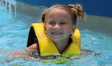 Little girl in Cyclone Zone with a life vest on smiling big