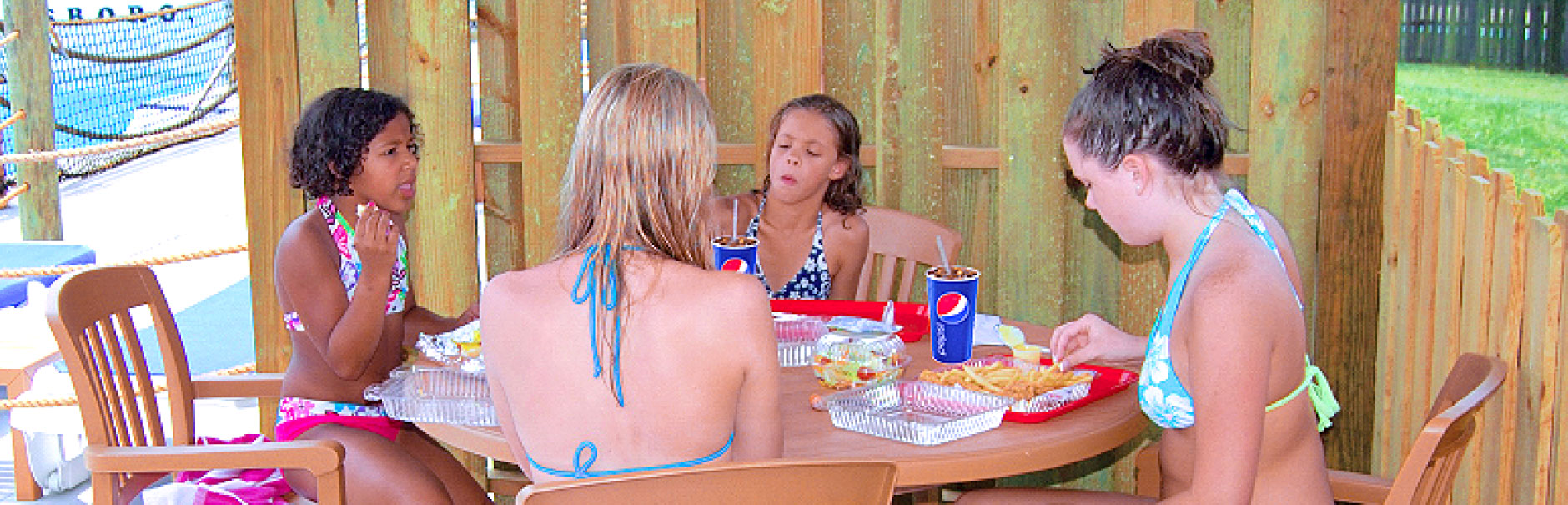 Four teenage girls eating around a table in a cabana.
