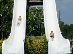 Two people sliding down very large water slides