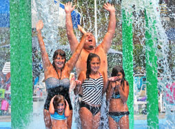 Two teenage girls with soak zone water blasters squarting a boy.
