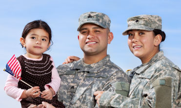 Two Military personnel,  one man and one woman, in uniforms smiling. One holding a little girl.