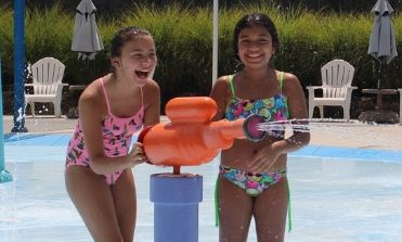 Two girls spraying the spray gun in Soak Zone and laughing