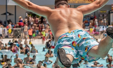A dad jumping straight out for a belly flop into a pool with a crowd in the background.