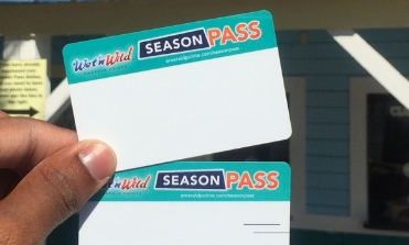 A person holding two season pass cards up in front of the Season Pass building.