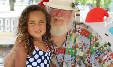 Santa with a little girl smiling at the camera