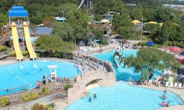 View of a few rides and pools with crystal blue water from the top of Double Barrel