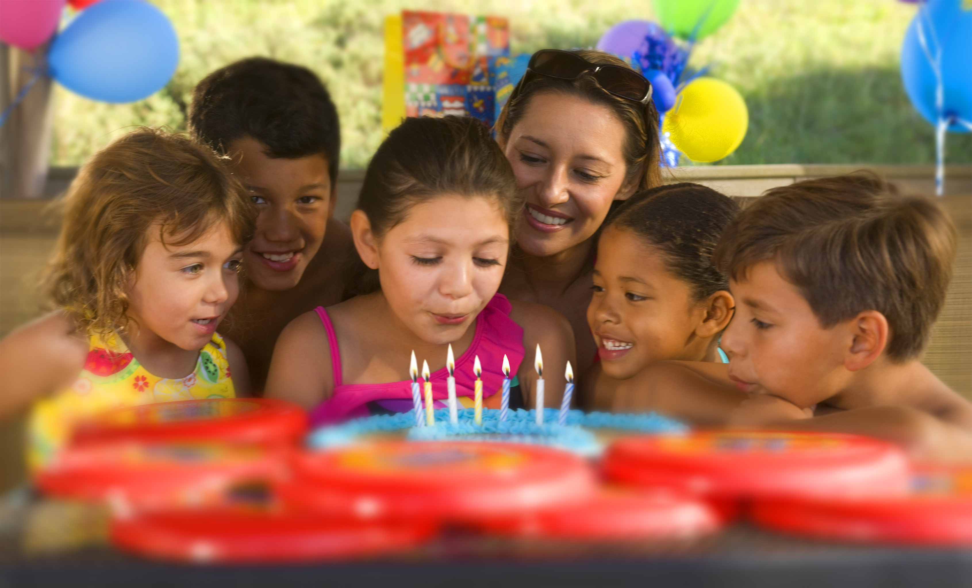 kids and a mom gathered around a cookie cake while the birthday kid blows out candles.