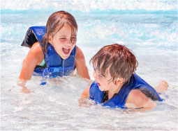 Two Kids Swimming with Lifejackets