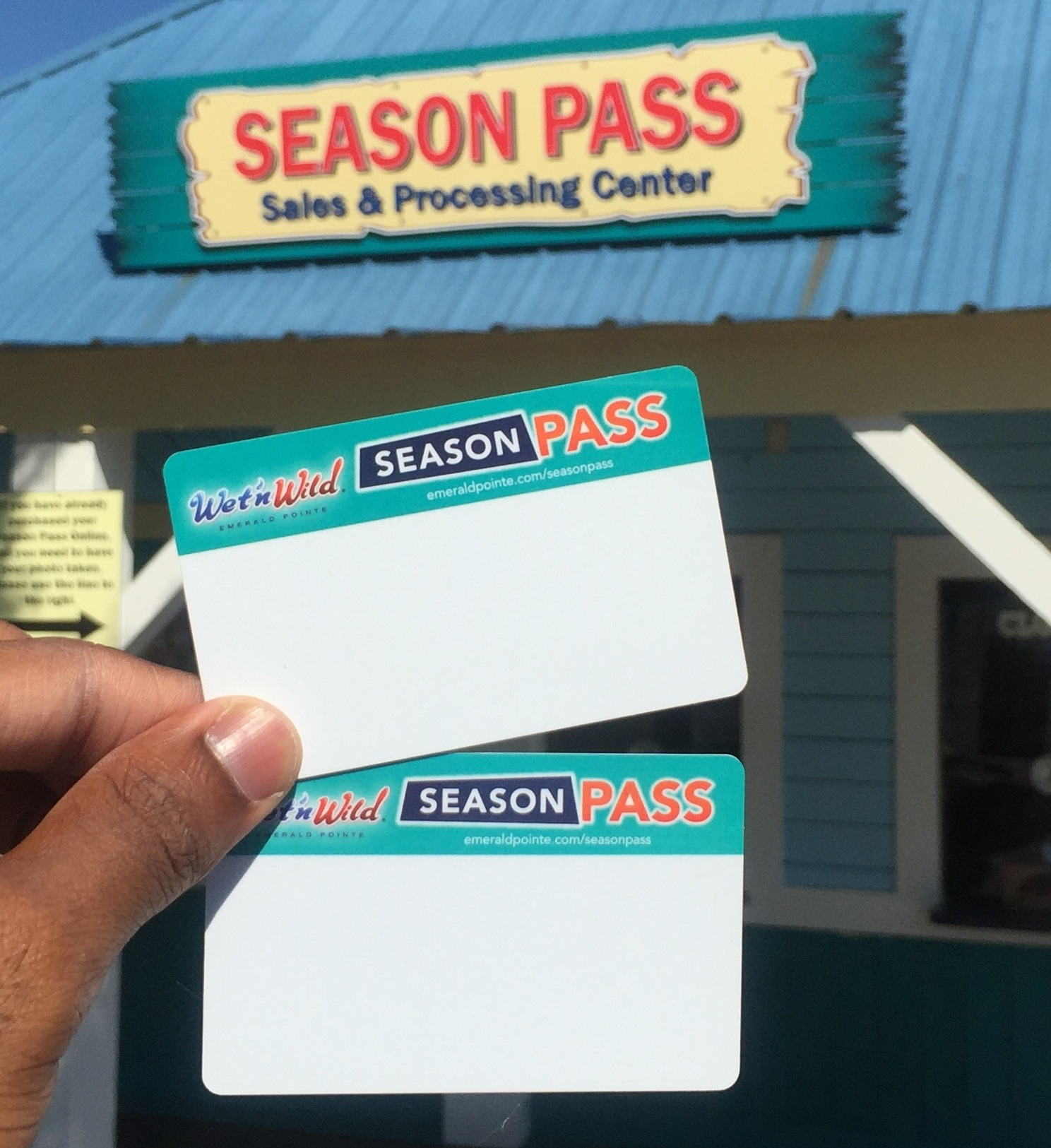 Two Season Pass Cards held up in front of the Season Pass building