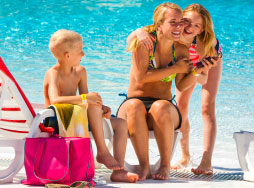 A mom with her two kids at a pool
