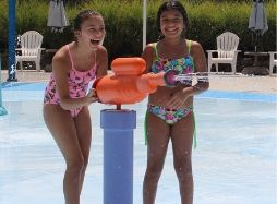 Two girls laughing in Soak Zone while they shoot our water gun