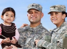 Military mom and dad with little girl smiling at camera