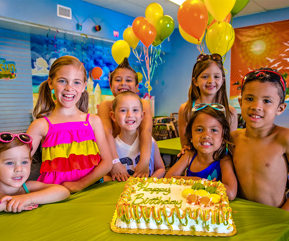 7 young boys & girls at a birthday table with a beautiful white, gold & green cake and balloons.