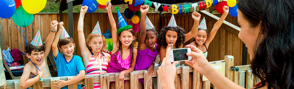 Seven young children smiling and standing in front of Birthday Party Cabana