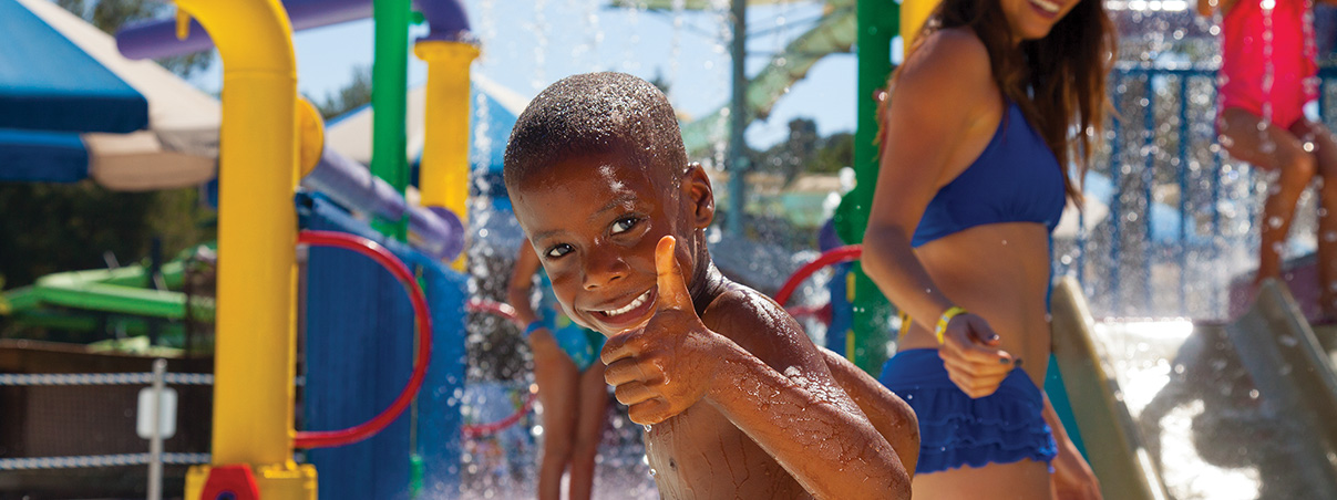 Child giving a thumbs-up in front of water slide
